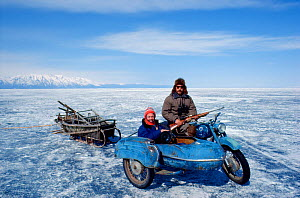 Cameraman Doug Allan on location in Lake Baikal, Siberia, with seal hunter and motorbike with sidecar pulling sledge. April 1989, Cover image of Freeze Frame  -  Doug Allan
