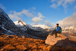 Woman sitting on rock admiring the view during the descent from Tom na Gruagaich, Beinn Alligin, Torridon, Scotland, UK, February 2010 Model Released. Did you know? Beinn Alligin is 260 million years... - Mark Hamblin / 2020VISION