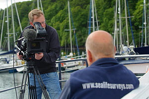Film-maker Raymond Besant filming an interview with Sea Life Surveys founder and proprietor Richard Fairbairns on board Sula Beag, a dedicated wildlife watching boat in Tobermory harbour, Isle of Mull...  -  Chris Gomersall / 2020VISION