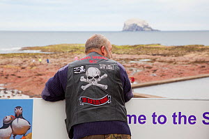 Biker wearing jacket with skull and crossbones emblem looking out over the Firth of Forth towards Bass Rock, North Berwick, Scotland, UK, July 2010  -  Peter Cairns / 2020VISION