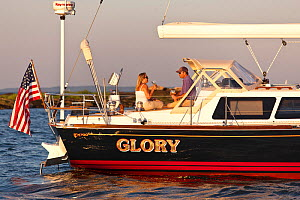 Couple enjoying a glass of wine on board Tartan sailing boat 'Glory', moored off the coast of Newport, Rhode Island, USA, July 2011. All non-editorial uses must be cleared individually.  -  Onne van der Wal