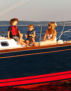 Woman and children relaxing on board Tartan sailing boat 'Glory', moored off the coast of Newport, Rhode Island, USA, July 2011. All non-editorial uses must be cleared individually.  -  Onne van der Wal