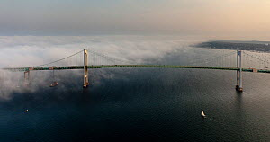 Aerial view of sailing boat approaching the Newport Bridge and a veil of thick, low cloud. Newport, Rhode Island, USA, July 2011. All non-editorial uses must be cleared individually.  -  Onne van der Wal