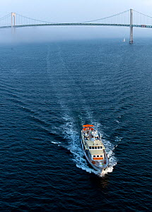 Aerial view of Highlander motor yacht with the Newport Bridge in its wake, Rhode Island, USA, July 2011. All non-editorial uses must be cleared individually.  -  Onne van der Wal