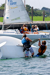Girl and boy attempting to right capsized Laser Bug dinghy at the Public Sailing Centre, Newport, Rhode Island, USA, August 2011. All non-editorial uses must be cleared individually.  -  Onne van der Wal
