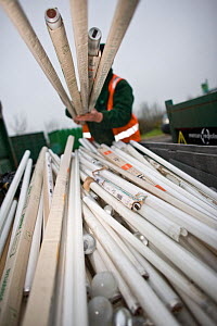 Man lifting fluorescent light tubes at a recycling centre, Stroud, Gloucestershire, UK, February 2008.  -  Nick Turner