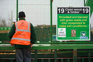 Workman next to infomation sign at wood recycling centre, where wood is made into soil conditioner, Gloucestershire, UK, February 2008.  -  Nick Turner