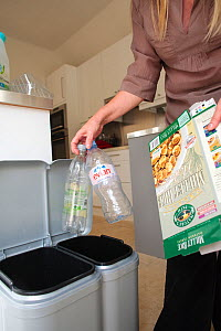 Woman putting plastic bottles and cardboard into kitchen recycling bins, September 2008.  -  Nick Turner