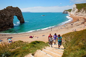 Family walking up steps from Durdle Door Beach onto the South West Coast Path National Trail, Dorset, UK, May 2009. - Nick Turner