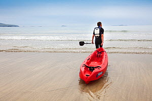 Man pulling his sea kayak into the sea at Caerfai Bay on the Pembrokeshire Coast Path, Wales, UK, June 2009 - Nick Turner