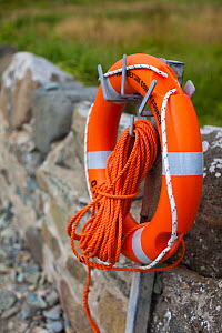 Lifebuoy attached to wall at Caerfai Bay on the Pembrokeshire Coast Path, Wales, UK, June 2009.  -  Nick Turner
