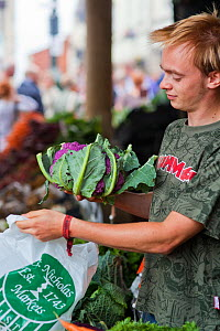 Man putting vegetables in bag at Stroud Farmers Market, Stroud, Gloucestershire, UK, August 2011. - Nick Turner