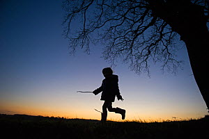 Young girl playing on edge of woodland, silhouetted against the sky, Norfolk, January 2012 Model released. Did you know? Children who spend more time playing outside are less likely to develop short-s...  -  David Tipling / 2020VISION