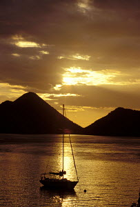 Yacht silhouetted at sunset off the coast of Tortola, British Virgin Islands, Caribbean. All non-editorial uses must be cleared individually. - Sea & See