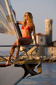 Woman relaxing on the bow of cruising yacht 'Pegasus', as she sails past Portoroz, Slovenia, July 2007. All non-editorial uses must be cleared individually. - Sea & See