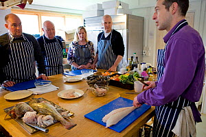 Group of people on a seafood cookery course run by Dorset-based Fraser Christian. People learn about fish and shellfish cookery skills with an emphasis on locally-caught sustainable species, Dorset, E...  -  Toby Roxburgh / 2020VISION