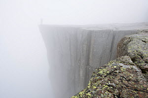 Person standing on Pulpit Rock, 604 meters above the Lysefjorden covered in mist, Rogaland, Norway  -  Roy Mangersnes