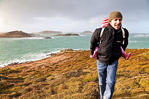 Man carrying child along footpath on a stormy day on St. Martin's, Isles of Scilly, UK, January 2012. No release available. - Merryn Thomas