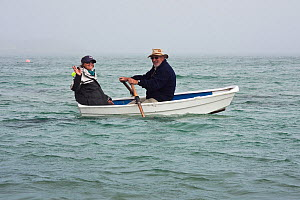 Couple in a small rowing boat in fog close to St. Martin's, Isles of Scilly, UK, June 2011. Model released. - Merryn Thomas