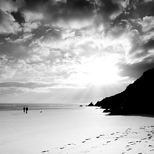 Silhouetted people walking along Three Cliffs Bay, Gower Peninsula, South Glamorgan, Wales, January 2012. No release available. - Merryn Thomas