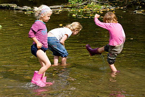 Children playing in River Onny,understanding nature by gathering river stones make oven for pizzas,Shropshire,England, UK 2011  -  David Woodfall