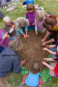 Adults and children making clay out of soil in order to make clay oven to make pizzas,learning how to use nature in a positive way,Shropshire, UK 2011  -  David Woodfall