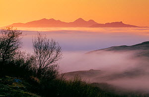 Islands of Rum and Eigg in the Inner Hebrides viewed from Ardnamurchan Peninsular through incoming sea fog at sunset, Argyll, Scotland, May 1999 - Laurie Campbell