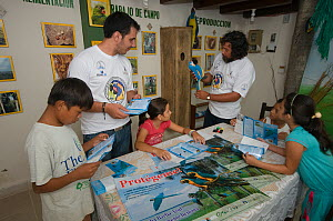 Conservation officers and children reading educational leaflets at the headquarters of the Programme for the Conservation of the Blue throated / Wagler's macaw (Ara glaucogularis) Trinidad, Beni, Boli...  -  Roland Seitre