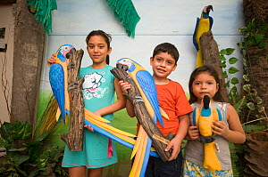 Children with macaw models at the Headquarters of the Programme for the Conservation of the Blue throated / Wagler's macaw (Ara glaucogularis) Trinidad, Beni, Bolivia, Critically endangered species, J...  -  Roland Seitre