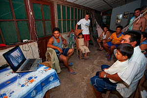 People gathered in front of laptop computer watching an educational programme on the conservation of the Blue throated / Wagler's macaw (Ara glaucogularis) Santa Ana del Yacuma, Beni, Bolivia, Critica...  -  Roland Seitre
