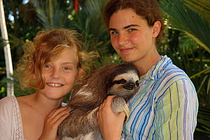 Two girls with tame Three-toed Sloth (Bradypus variegatus), 'Buttercup'.   Aviarios del Caribe Sloth Sanctuary, Costa Rica, 2008.  -  Roland Seitre
