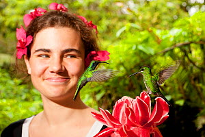 Girl watching two Green-crowned Brilliant Hummingbirds (Heliodoxa jacula) at flower. Captive. La Paz Waterfall Gardens, Poas, Costa Rica. Model released - Roland Seitre
