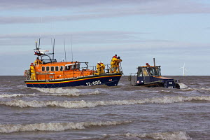 Lifeboat crew attaching line from tractor during recovery of the Hoylake RNLI Lifeboat 'Lady of Hilbre'. Hoylake, Wirral, Merseyside, United Kingdom, February 2012. For editorial use only. - Graham Brazendale