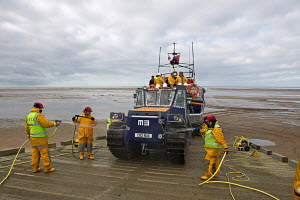 Crew cleaning tractor, trailor and lifeboat following exercise on board the Hoylake RNLI Lifeboat 'Lady of Hilbre'. Hoylake, Wirral, Merseyside, United Kingdom, February 2012. For editorial use only. - Graham Brazendale