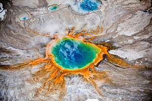 Aerial view of Grand Prismatic thermal spring in Yellowstone National Park, USA. The bright colours are natural, coming from thermophile bacteria in the water. People can be seen walking on the raised...  -  Paul D Stewart