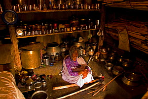 An elderly Toda woman sits inside her hut preparing a meal of raagi on a traditional wood-burning stove. Todas are strict vegetarians and their diet consists largely of plant and milk products. Wester... - Sandesh Kadur