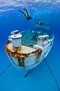 Divers on scooters exploring the wreck of the USS Kittiwake (US Military submarine rescue vessel)  Photograph was taken shortly after the wreck was deliberately sunk as an attraction for scuba divers,...  -  Alex Mustard