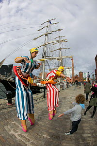 Performers on stilts entertaining child during tall ships event at Liverpool River Festival. Albert Dock, River Mersey, England, September 2011. All non-editorial uses must be cleared individually.  -  David Woodfall