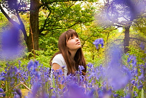 Girl sitting amongst flowering Bluebells (Hyacinthoides non-scripta) in woodland, Cumbernauld Glen, North Lanarkshire, Scotland, UK, May 2011. 2020VISION Exhibition. - Katrina Martin / 2020VISION