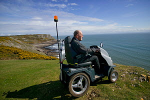 Disabled Man in his 80's enjoying stunning coastal scenery from Pennard cliff using 'Tramper ' machine designed to aid mobility to difficult places for disabled people, Gower, South Wales, UK 2009  -  David Woodfall