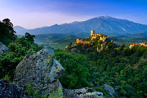 The village of Eus perched on a hilltop with sunlight with the Pic de Canigou beyond, the Pyrenees, Languedoc-Rousillon, France. June 2006. - David Noton