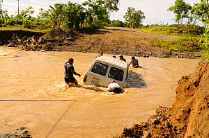 Group of men attempting to rescue a vehicle stuck in flood water, River Camerones, Manabi province Ecuador. February 2012. No release available.  -  Will Watson