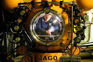 Man looking out of view port of the German research submersible JAGO, aboard the RV POSEIDON, September 2011, editorial use only. Photo taken in cooperation with GEOMAR coldwater coral research projec... - Solvin Zankl / GEOMAR