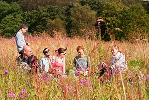 Young people having a picnic and making heart gestures at the camera, Luggiebank Wood SWT reserve, North Lanarkshire, Scotland, UK, August  2011  -  Katrina Martin / 2020VISION