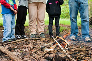 Five people standing next to a small fire on a bushcraft day, Palacerigg Country Park, Cumbernauld, North Lanarkshire, Scotland, UK, July  2011  -  Katrina Martin / 2020VISION
