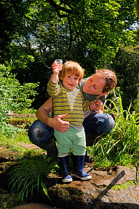 Young boy held by mother as he holds up a collecting pot after a pond-dipping session during Abbots Pool and woodland reserve Bioblitz, Bristol, June, Bristol, UK, June 2012. Model released.  -  Nick Upton / 2020VISION