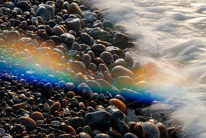 Waves of the Baltic sea washing over pebbles creating a  rainbow from the spray, Nienhagen, Germany, April  -  Sandra Bartocha