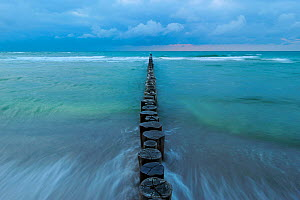 Waves washing around line of Wooden posts running into the Baltic Sea at dusk, National ParkVorpommersche Boddenlandschaft, Germany, May  -  Sandra Bartocha
