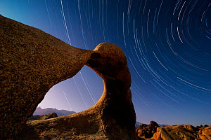 Star trails in sky over Alabama Hills, BLM eroded granite formation know as Mobius Arch. Eastern Sierra, California. May 2012. - Jack Dykinga