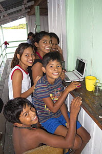 Children using a laptop on a floating house on the Rio Negro, Amazonia, Brazil, June 2012  -  Doc White